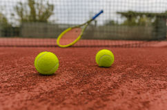 Tennis balls on court. Tennis balls on clay court with blurred tennis racket and net in the background Stock Photo