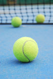 Tennis balls on court with net. Tennis balls on blue court field Royalty Free Stock Photography