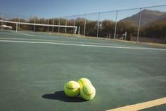 Tennis balls on empty court Royalty Free Stock Image