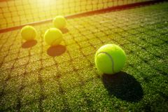 Tennis balls on grass court with sunlight. Tennis balls and net on grass court with sunlight from the back royalty free stock photography