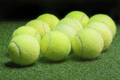 Tennis balls on green artificial grass surface Stock Image