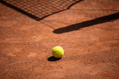 Tennis balls on the ground of clay court Stock Photos