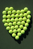 Tennis balls heart. The shape of heart made of tennis balls arranged on dark green background Stock Images