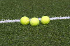 Tennis balls lays on grass court line Royalty Free Stock Photos