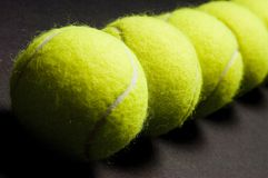 Tennis Balls Macro 2. A macro shot of a line of tennis balls on a dark background. Shallow depth of field used Stock Image