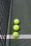 Tennis balls by the net. Bright yellow tennis balls on the court by a black net Royalty Free Stock Photos