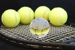 Tennis balls and one globe stock image