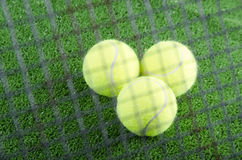 Tennis balls on prison. Tennis balls and rackets on artificial grass Royalty Free Stock Images