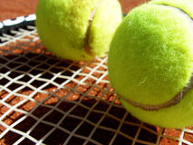 Tennis balls and racket. Tennis balls on a racket - on the court ground Stock Photography