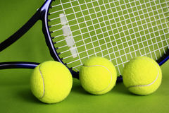 Tennis balls and racket. On a green background Royalty Free Stock Photo