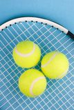 Tennis balls with racket. Three tennis balls and racket on blue background Stock Images