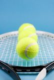 Tennis balls with racket. Three tennis balls and racket on blue background Royalty Free Stock Image