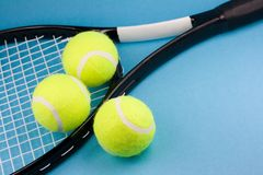 Tennis balls with racket. Three tennis balls and racket on blue background Royalty Free Stock Images