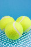Tennis balls with racket. Three tennis balls and racket on blue background Royalty Free Stock Photos