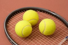 Tennis balls and racket. Three tennis balls on a racket head stock photos