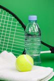 Tennis balls with racket, bottle and towel. Tennis balls, racket, bottle and towel on green background Royalty Free Stock Photos