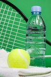 Tennis balls with racket, bottle and towel. Tennis balls, racket, bottle and towel on green background Stock Photos
