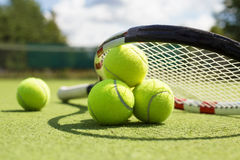 Tennis balls and racket on the grass court Royalty Free Stock Photo