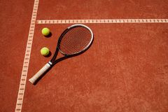 Tennis balls and racket on red dross. Close up of tennis balls and racket on red dross court stock photo