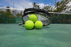 Tennis balls and racquets on court. Tennis balls and racquets on the court close-up Royalty Free Stock Image