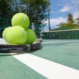 Tennis balls and racquets on court. Tennis balls and racquets on the court close-up Royalty Free Stock Images
