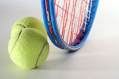 Tennis Balls and Raquet. Tennis raquet and two balls on light background Royalty Free Stock Image