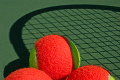 Tennis balls and shadow racket. Yellow-red balls on a green tennis court Royalty Free Stock Photography