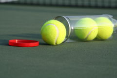 Tennis balls on tennis court. A view of three new yellow tennis balls in a clear plastic cannister lying on the green surface of a tennis court Royalty Free Stock Image