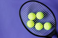Tennis balls under black racquet. Violet background. Concept sport. Copy space Stock Photography