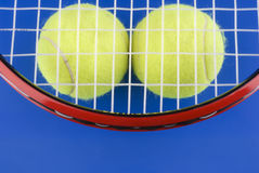 Tennis balls is under a tennis racket on a blue Royalty Free Stock Photography