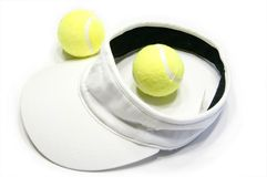 Tennis balls and visor cap. Tennis racquet and balls isolated on a white background Royalty Free Stock Image