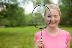 Tennis biondo della tenuta della ragazza - maglietta d'uso del pinck della racchetta Fotografia Stock Libera da Diritti