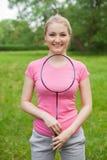 Tennis biondo della tenuta della ragazza - maglietta d'uso del pinck della racchetta Immagine Stock