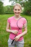 Tennis biondo della tenuta della ragazza - maglietta d'uso del pinck della racchetta Immagini Stock Libere da Diritti