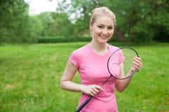 Tennis biondo della tenuta della ragazza - maglietta d'uso del pinck della racchetta Immagini Stock