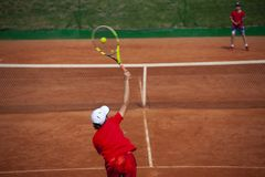 Tennis boy serving in singles tennis tournament. stock photos