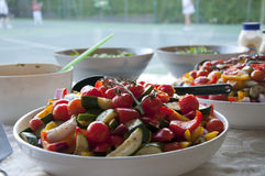 Tennis club salad. A delicious salad with vine tomatoes, yellow and red peppers, corgettes and red onion waiting for the tennis players in the background stock photos