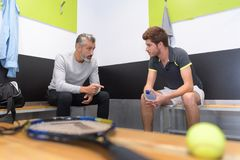 Tennis coach talking to player in changing room. Tenis Royalty Free Stock Image