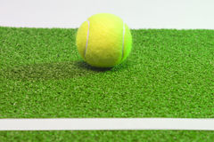 Tennis coconcept. Ball, line and grenn grass tennis court.horizo Stock Images