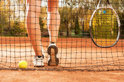 Tennis concept with ball, netting, racket and woman legs Royalty Free Stock Photo