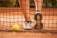 Tennis concept with ball, netting and woman feet Stock Image