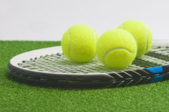 Tennis concept: closeup, tennis racket with balls lies on green Stock Images