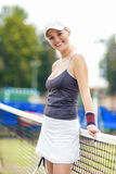 Tennis Concept: Portrait of Positive Smiling Professional Female. Tennis Player Posing with Racquet near Net. Vertical Composition Royalty Free Stock Photo