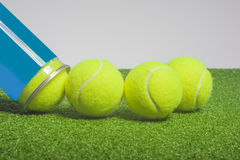 Tennis concept: tennis balls out of a container lie on green art Royalty Free Stock Photo