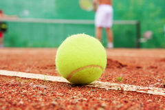 At tennis court. Yellow tennis ball at a line of tennis court Royalty Free Stock Image