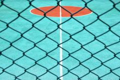 Tennis court behind surround net Royalty Free Stock Photo