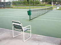 Tennis court and a chair. Outdoors tennis court on a sunny day, with a chair in the foreground Stock Images