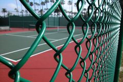 Tennis Court Through Fence. Foreground shot of a green fence surrounding a traditional tennis court at a tennis club in California Royalty Free Stock Image
