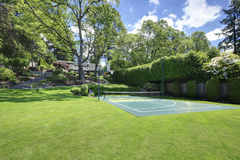 Tennis court with house on the hill and bright green grass. Royalty Free Stock Photo