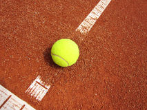 Tennis court line with ball. Yellow tennis ball on the t-line Royalty Free Stock Photos